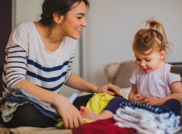 A mother smiles as she folds laundry on the bed with her young daughter.