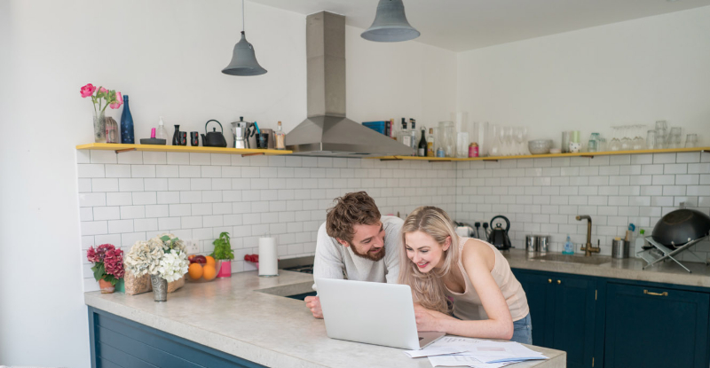 A man and woman lean onto their kitchen counter to look at a laptop together.