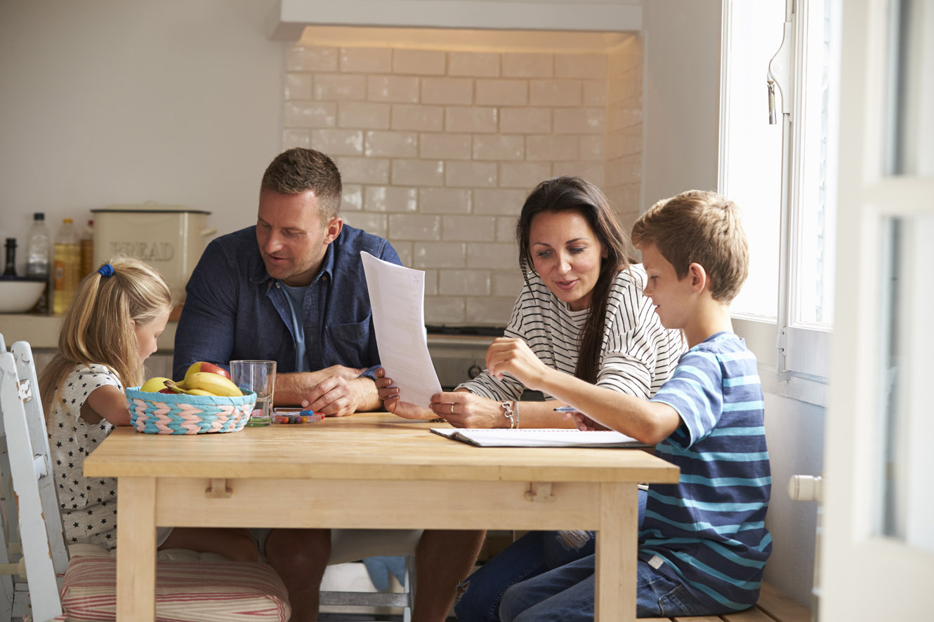 A family sitting at a table working on homework together.