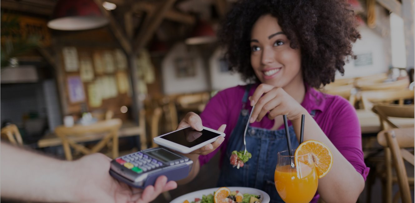 Smiling young woman using mobile payment at restaurant