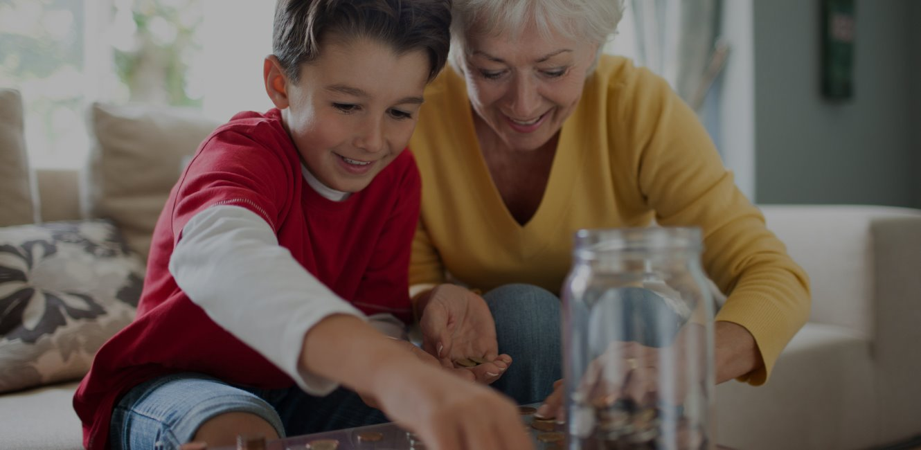 Grandmom and grandson counting change for savings jar