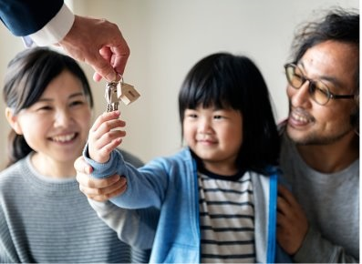 Asian family buy a new house, young girl receiving keys.